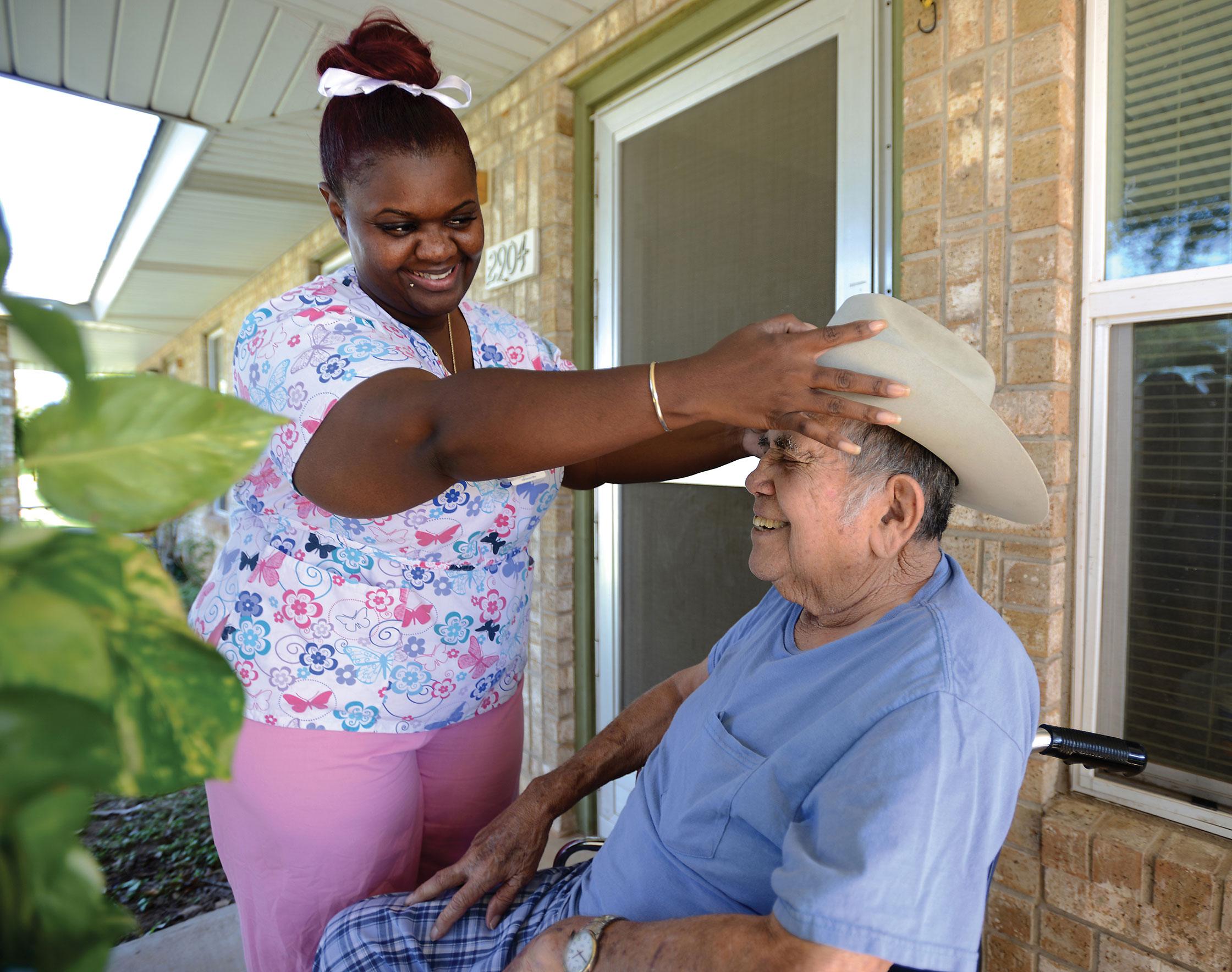 A Compassus nurse places a hat on a patient's head